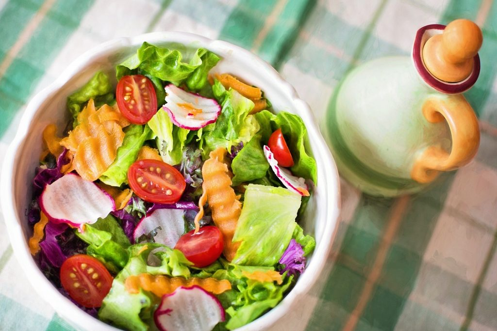 bowl of salad and jug of oil: healthy food choices