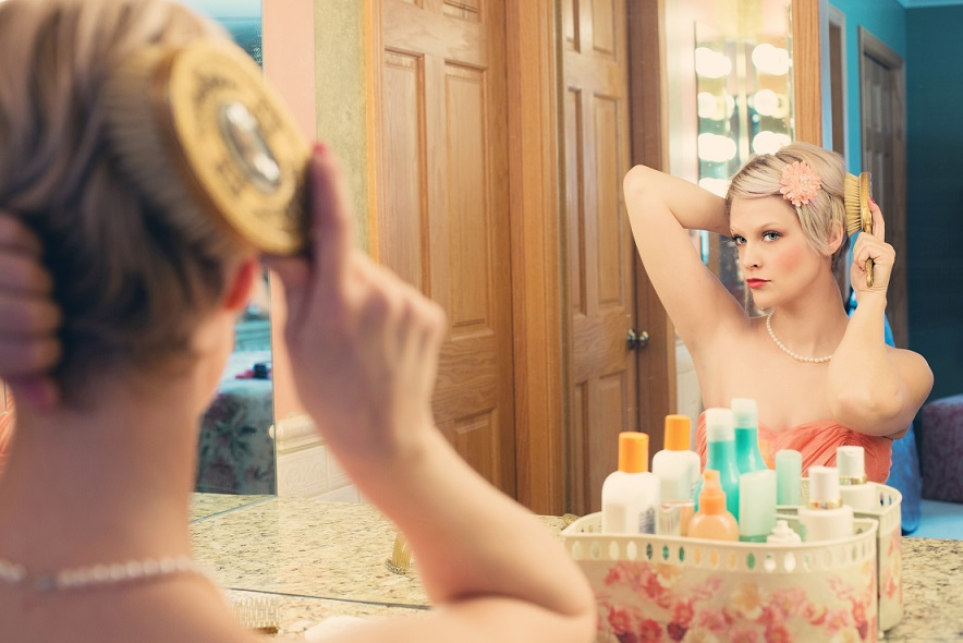 woman brushing here her in front of a mirror