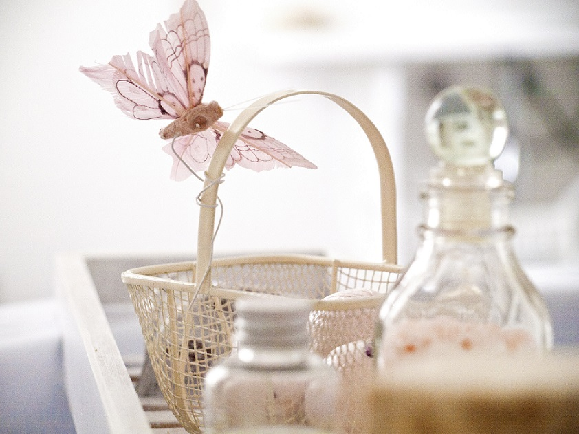 basket with cloth butterfly and various glass bottles