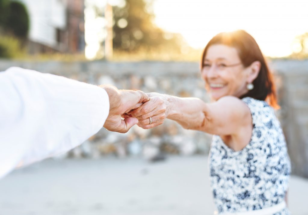 older woman holder hands with a man out of picture