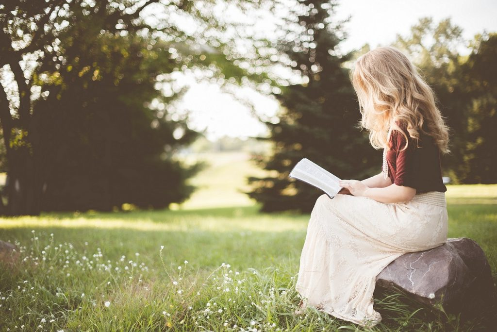 a young lady reading a book in the great outdoors