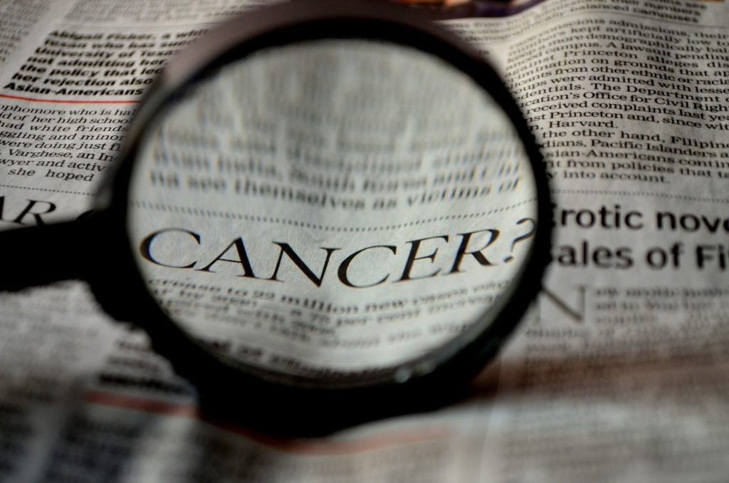 "magnifying glass showing the word ""Cancer"""