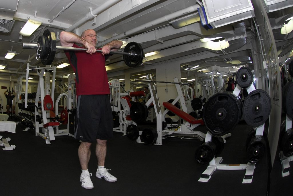 an older man doing weights in a well equipped gym